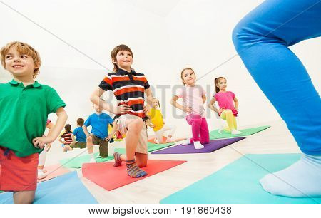 Group of 5-6 years old kids doing kneeling exercises at physical education lesson in gym