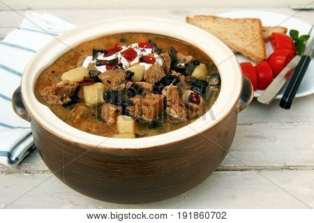 Goulash pot with potatoes and mushrooms, cream and red pepper on top