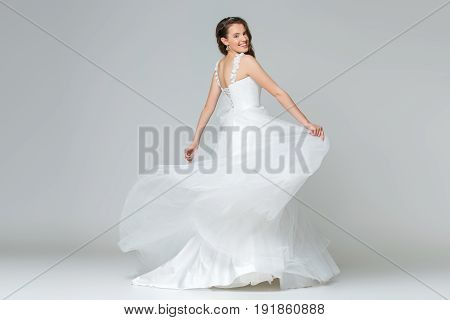 beautiful happy young bride in long white wedding gown. Studio shot on grey background. Copy space.