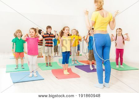 Group of happy kids jumping ropes with sports teacher at gym lesson