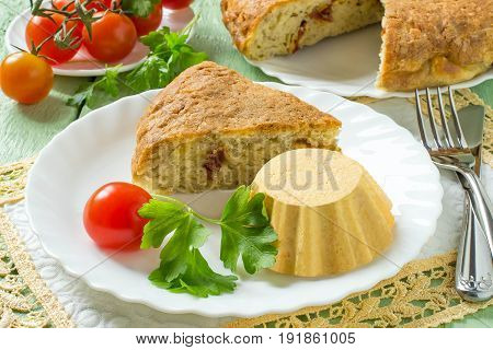 Tasty homemade cheese cake with dried tomatoes and carrot-chicken souffle cooked in double boiler. Green wooden table yellow napkin piece of cheese and fresh cherry tomatoes. Selective focus