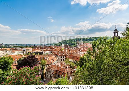 Panorama of houses with traditional red roofs and trees in Prague Mala Strana district in the Czech Republic during sunny summer day.