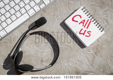call center manager work place for call us concept with headset on stone desk background top view