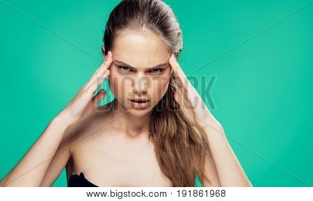 Woman holding her head, woman on green background portrait.