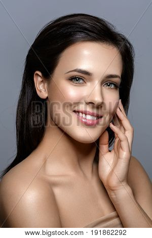 Beautiful happy young woman with healthy glowing skin and natural makeup touching face. Beauty shot on grey background. Copy space.