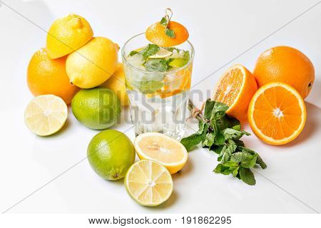 Summer drink. Traditional lemonade with lemon mint and ice on white table. Top view with soft focus.