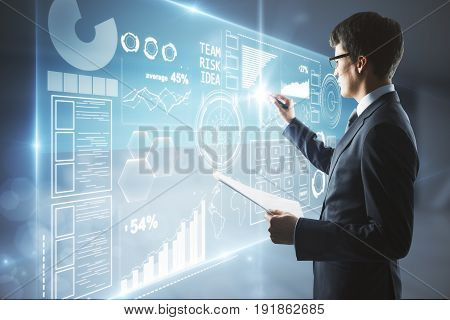 Side view of young businessman holding document and drawing business screen in blurry interior. Future concept. 3D Rendering