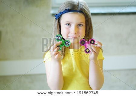 Little Beautiful Girl In Yellow T-shirt Is Playing With Two Spinners In Hands