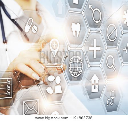 Side view of female doctor's hand pointing at abstract digital icons. Innovation concept