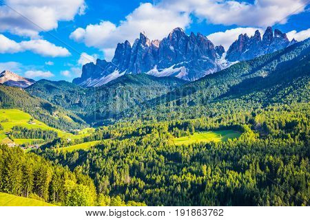Warm autumn in the Dolomites, the Val de Funes. The concept of ecological tourism. The valley is surrounded by a dentate wall of dolomite rocks