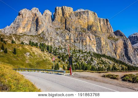 Impressive ridge of dolomite rocks. Picturesque highway through the Sella Pass. Autumn in the Tirol, Dolomites. The concept of ecological and extreme tourism