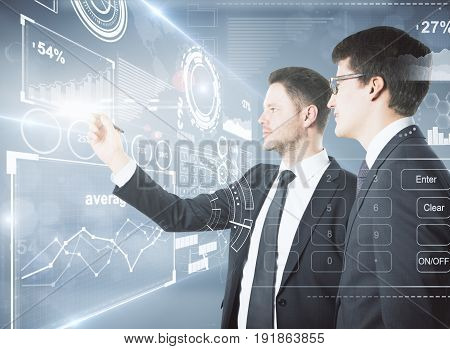 Side view of two handsome young businessmen drawing abstract digital business screen in blurry interior. Partnership concept. 3D Rendering