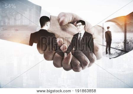 Close up of abstract handshake on city bakcground. Contract concept. Double exposure
