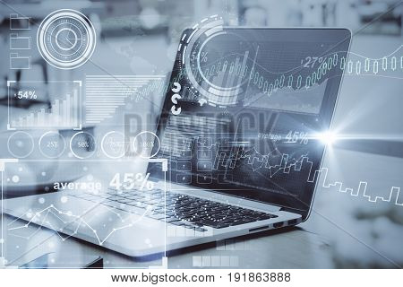 Side view of laptop with digital business charts placed on desktop with coffee cup. Toned image. Fintech concept
