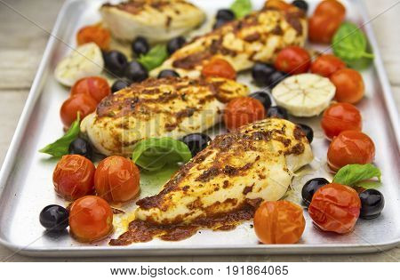 Chicken breast with harissa, tomatoes and black olives
