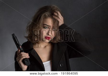 scared beautiful girl with gun holds her head on black background