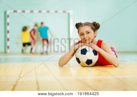 Portrait of happy preteen girl, football player, laying on the floor of sports hall with soccer ball