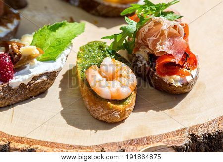 Sandwich with shrimps and fresh vegetables on wooden board