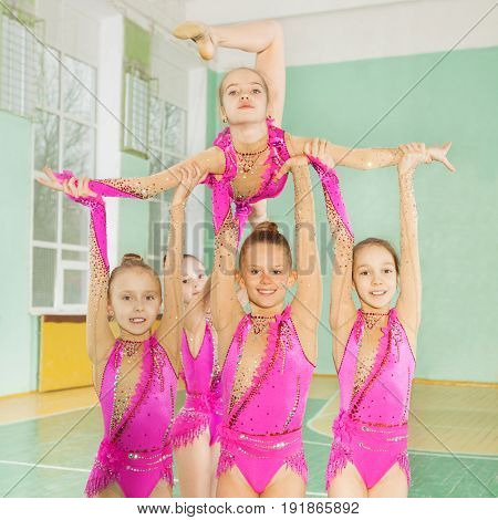 Close-up portrait of six happy girls carrying out their routine in a rhythmic gymnastics event