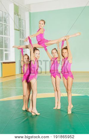 Rhythmic gymnastics group of six preteen girls showing their stretching and flexibility