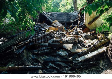 A pile of garbage, trash, ruins and rotten tires on background of abandoned building