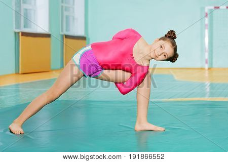 Cute preteen girl doing stretching exercise on mat in school gymnasium