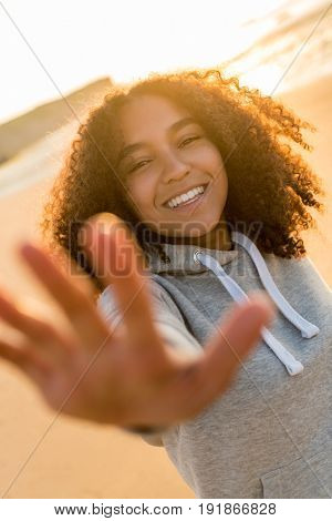 Outdoor portrait beautiful happy mixed race African American girl teenager female young woman on beach reaching out to camera, smiling and laughing with perfect teeth in golden sunset evening sunshine