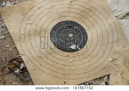 Shooting shield with holes from shots. The old worn shot target dial.