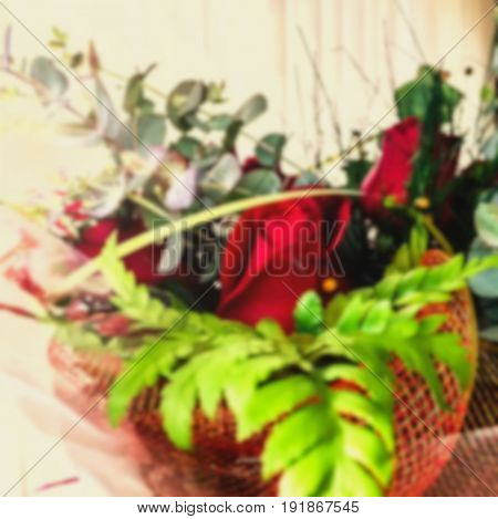 Blured view of gift bouquet of red roses in a wicker basket