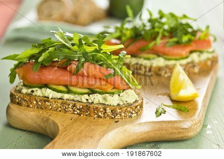 Open face sandwich with cottage cheese, cucumber, rucola and smoked salmon