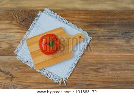 One fresh red ripe tomato with water drops on branch on wooden background with rustic wooden chopping board in center, white linen napkin. Top view, copy space