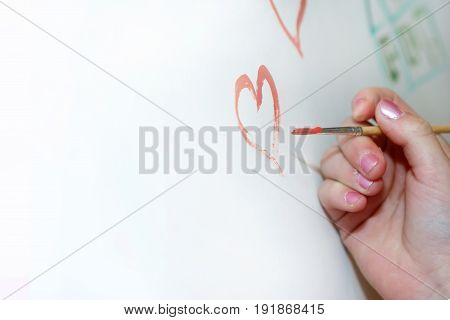 Drawing paint on paper. Hand drawing a heart. The artist draws with a brush.