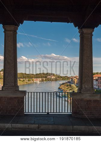 Glimpse of river Ticino in Pavia through the openings of Ponte Coperto