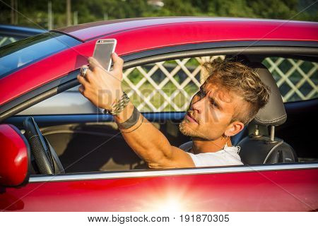 Close up Handsome Young Man Showing a Toothy Smile While Talking Selfie Photo Using his Phone Inside his Car.