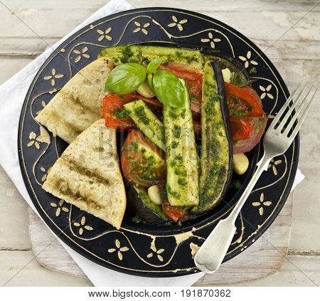 Ratatouille - aubergine, courgette and tomatoes with green pesto and fresh bread on black wooden plate