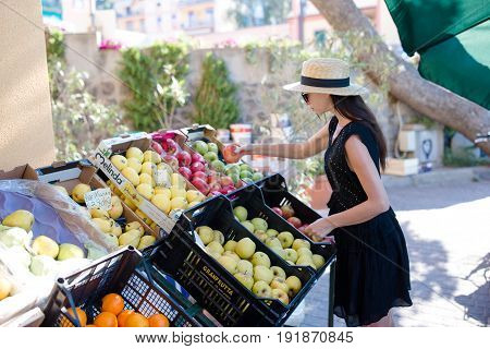 Woman buying fruits and vegetables at farmers market. Portrait of young woman shopping for healthy lifestyle.
