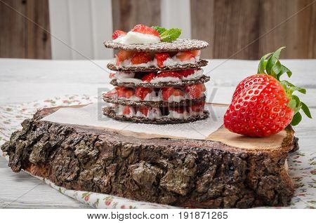 Chocolate belgian waffles with strawberries whipped cream and mint leaf on wooden table