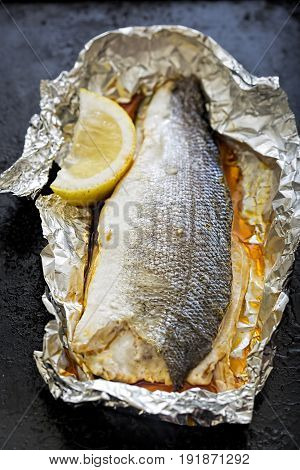 Baked grilled seabass fish with lemon in foil