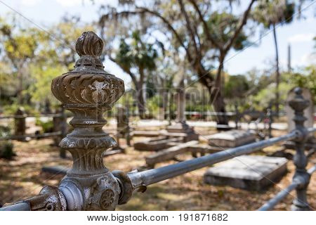 Historic Bonaventure Cemetery in Savannah GA. Old rusty wrought iron post and fence. Selective focus on foreground to accommodate copy if needed.