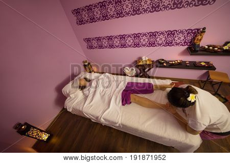 Masseur does thai massage for woman on couch in spa room with decoration, above view