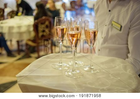 Waiter holds tray with white sparkling wine during event, noface, people out of focus