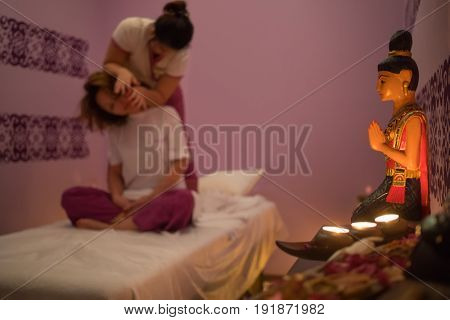 Masseur does thai massage for woman on couch in spa salon with lanterns, focus on statue