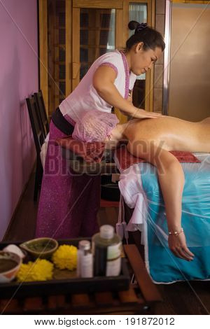 Woman does thai massage with sand and oils for woman on couch in spa room