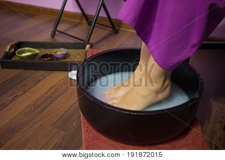 Female feet in warm aromatic water in wooden bowl in room of spa salon