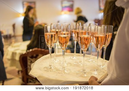 Waiter holds tray with white wine during event, noface, people out of focus
