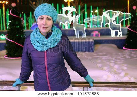 Happy woman stands on ice rink outdoor at night, decorative lighting animals out of focus