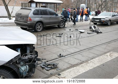 Group car accident with many damages on street, people out of focus at winter