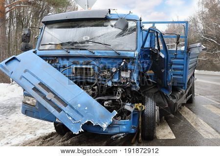 Damaged big truck after car accident with many damages on road at winter