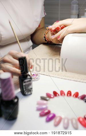 Manicurist hands make design manicure for woman in salon with UV lamp