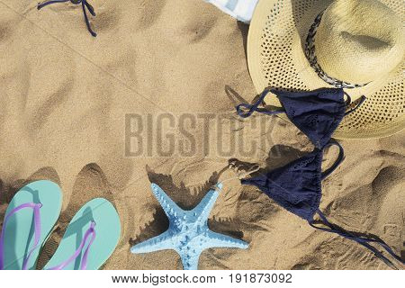 Summer beach fun - sandals with starfish, hat and swimming suit on beach sand